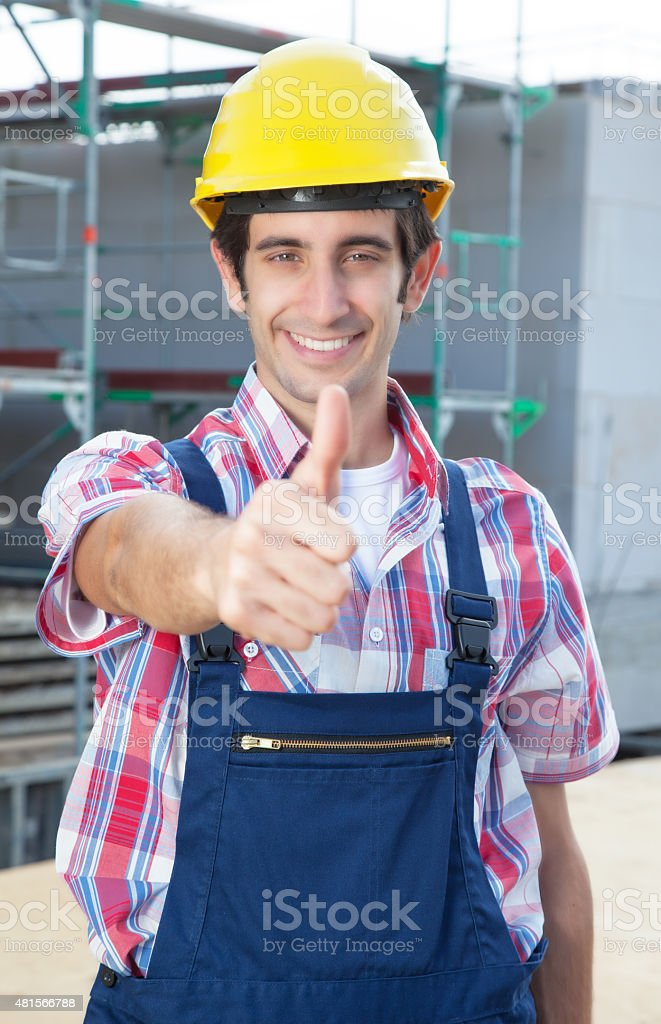 Hispanic construction worker at building site with showing thumb up stock photo