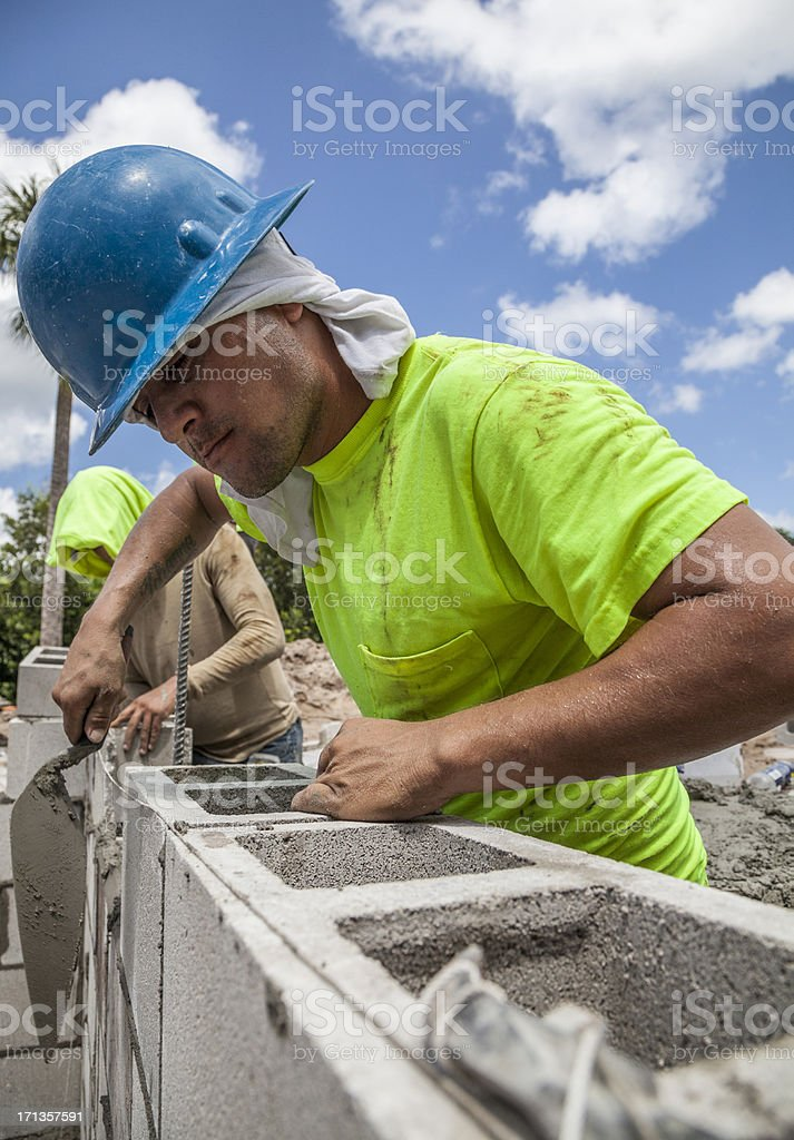 Hispanic Construction Worker Building Cement Block Wall stock photo