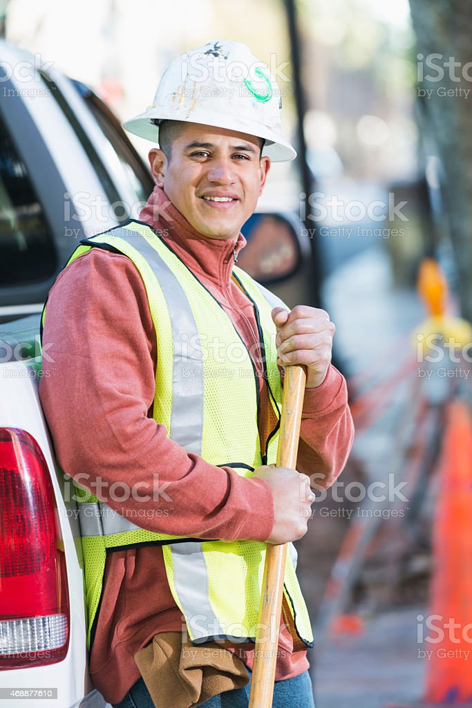 Hispanic construction worker with pickup and shovel stock photo
