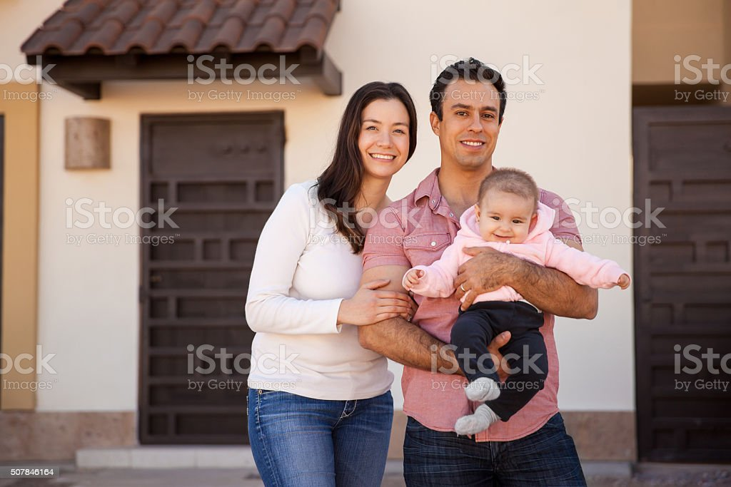 Hispanic couple and baby in their new home stock photo