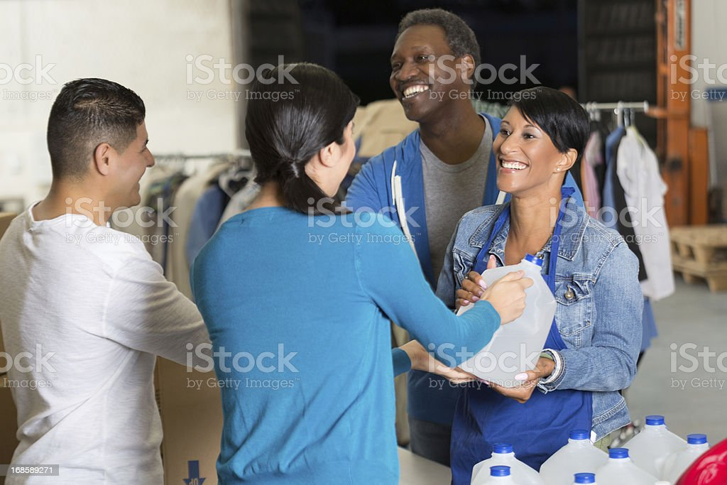 Hispanic couple donating water and blankets at disaster relief charity stock photo