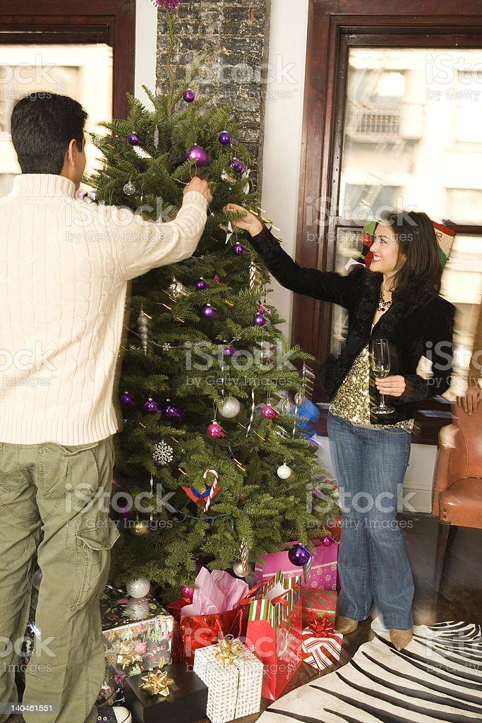 Hispanic couple hanging ornaments on a christmas tree royalty-free stock photo