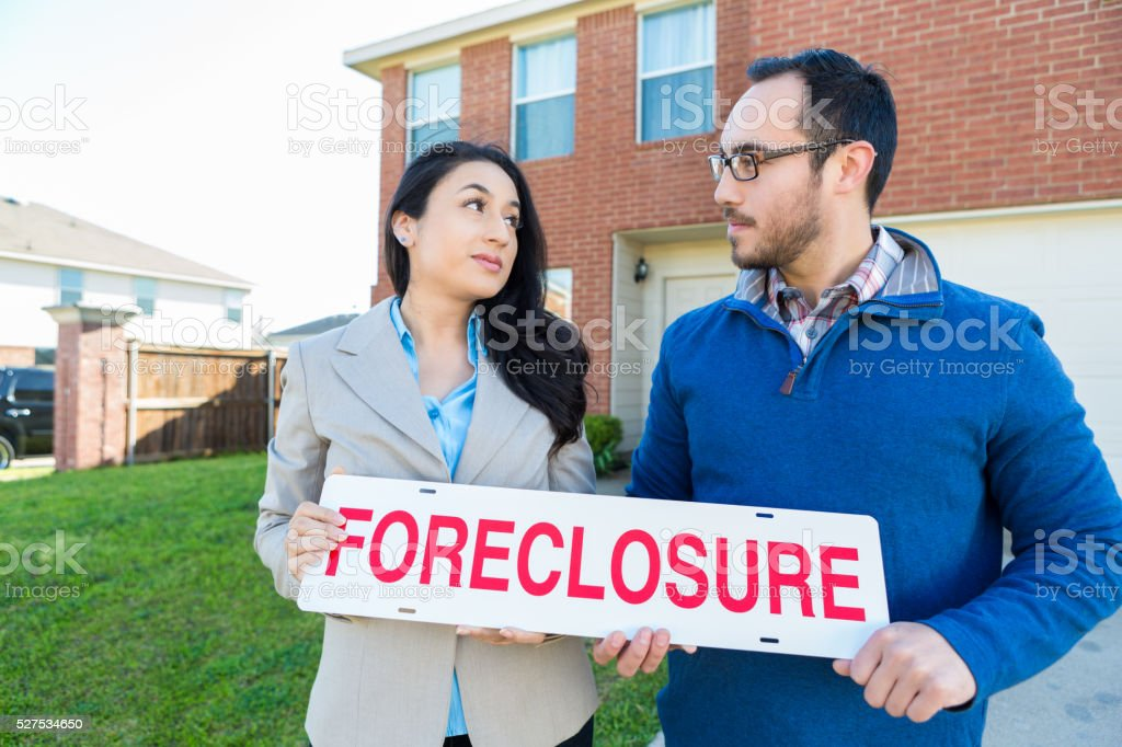 Hispanic couple hold forclosure sign in front of house stock photo