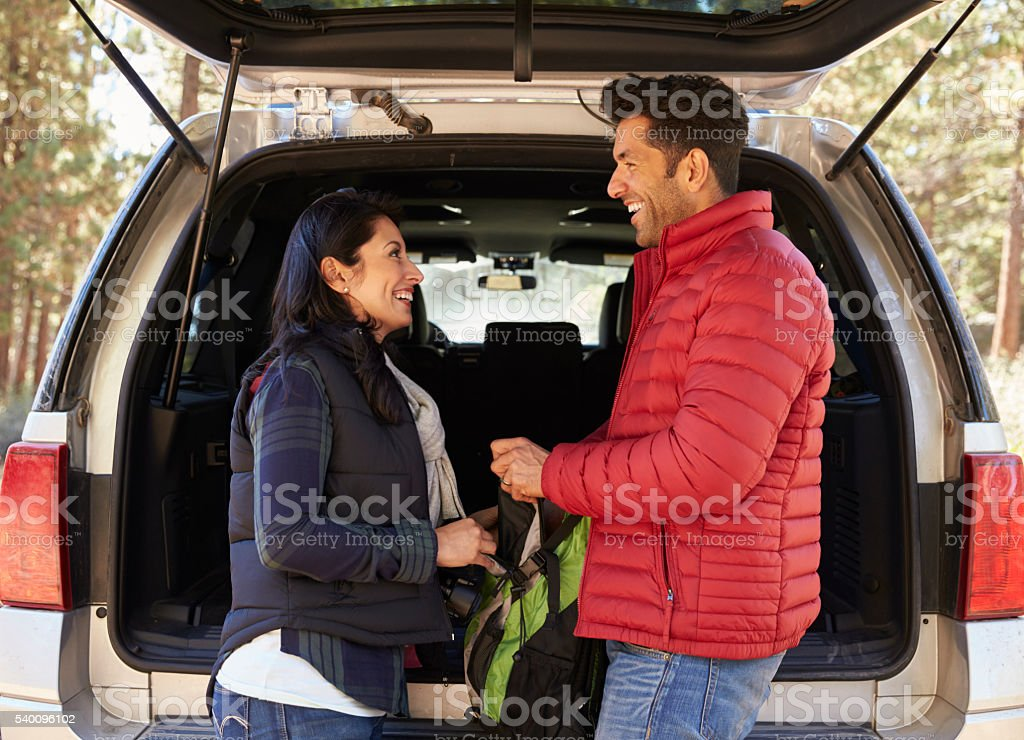 Hispanic couple looking at each other beside open back car stock photo