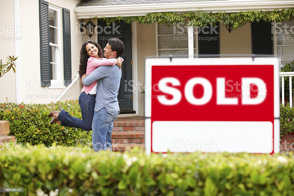 Hispanic couple outside home with sold sign royalty-free stock photo