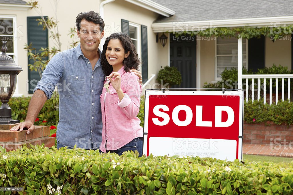Hispanic couple outside home with sold sign stock photo
