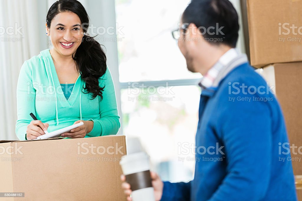 Hispanic couple pack moving boxes together stock photo