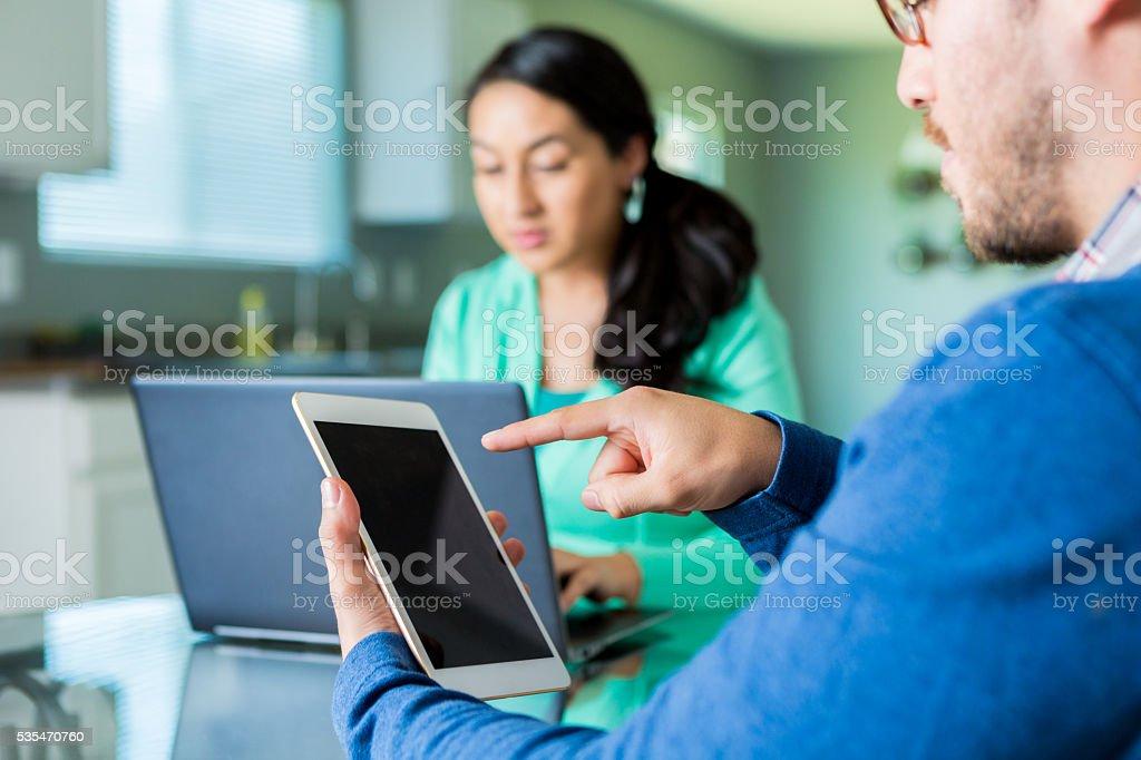 Hispanic couple using technology at kitchen table stock photo