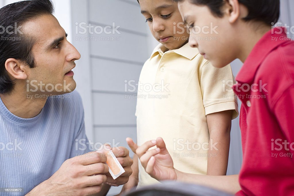 hispanic dad giving a band aid to his young son royalty-free stock photo