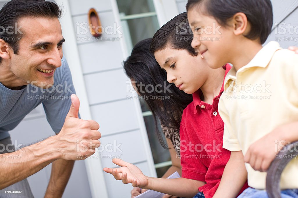hispanic dad giving his family a thumbs up royalty-free stock photo