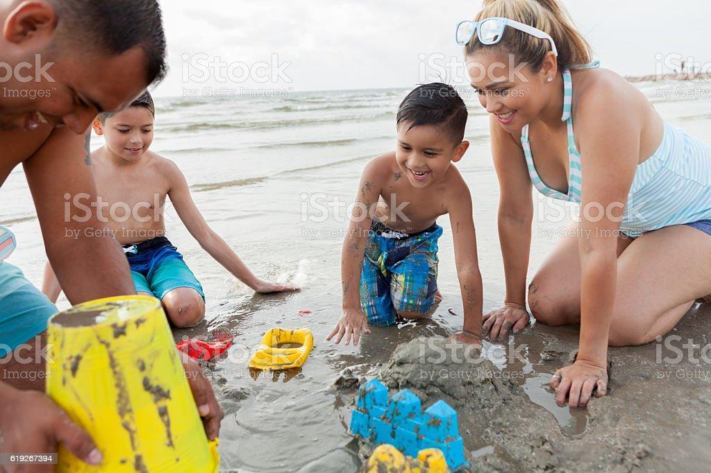 Hispanic dad helps his sons build sandcastle stock photo