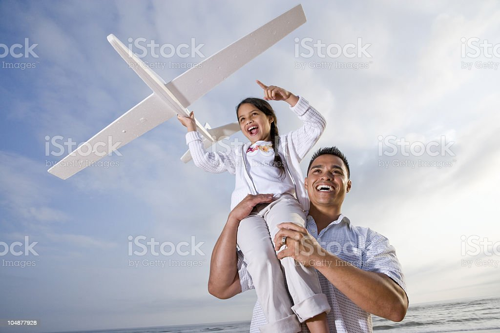 Hispanic dad playing holding girl high on shoulder royalty-free stock photo