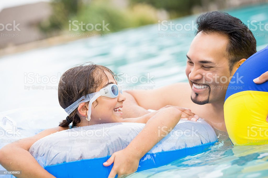 Hispanic dad swimming in pool with his daughter royalty-free stock photo