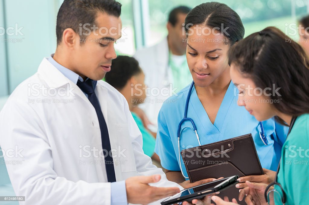 Hispanic doctor discusses patient with colleagues stock photo