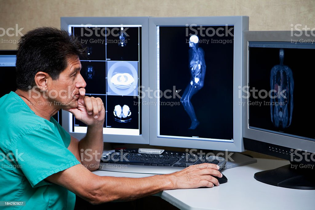 Hispanic doctor with medical scans stock photo