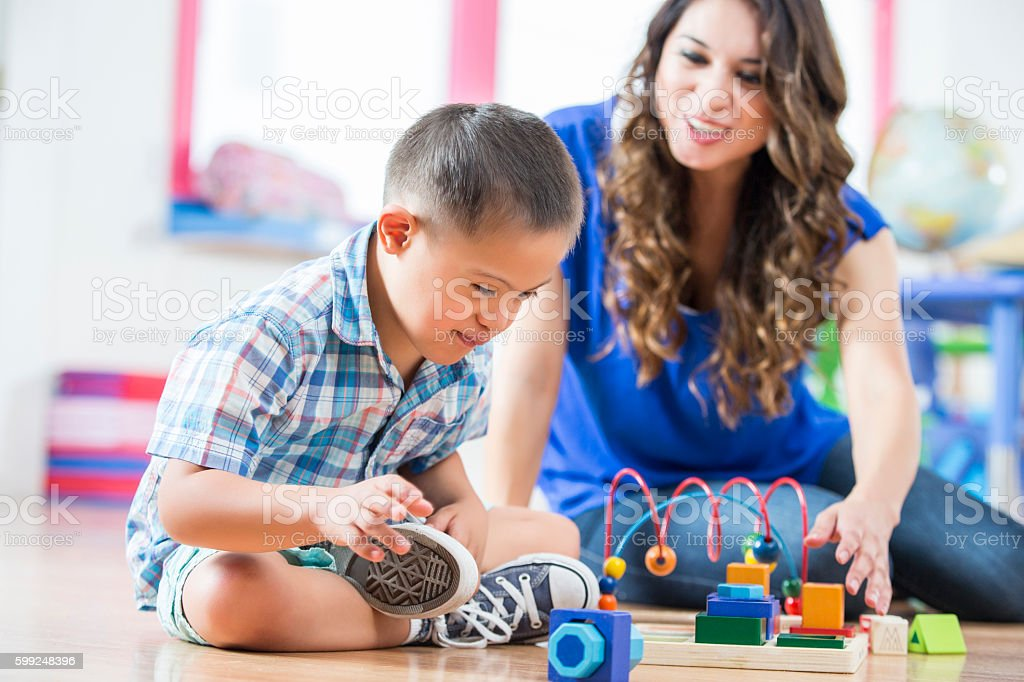 Hispanic Down Syndrome boy reaching for toys at daycare center stock photo