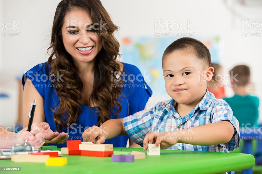 Hispanic Down Syndrome child playing with blocks at daycare stock photo