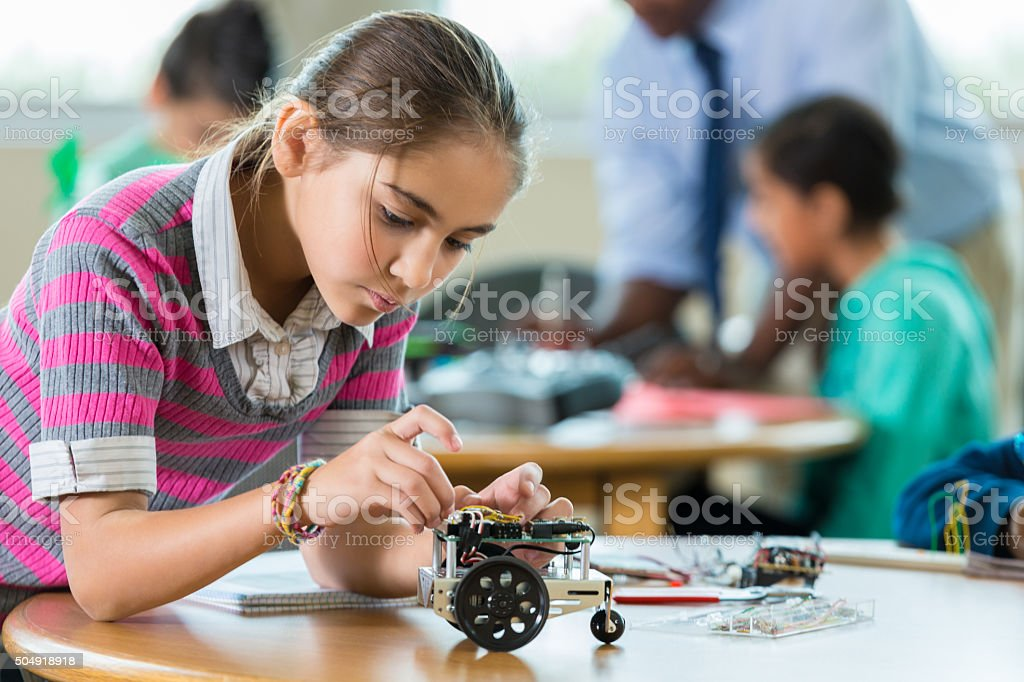 Hispanic elementary student building robot during science class stock photo