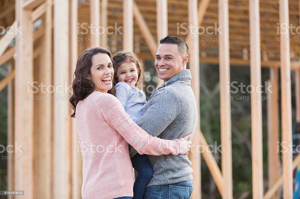 Hispanic family building a new home, happy girl stock photo