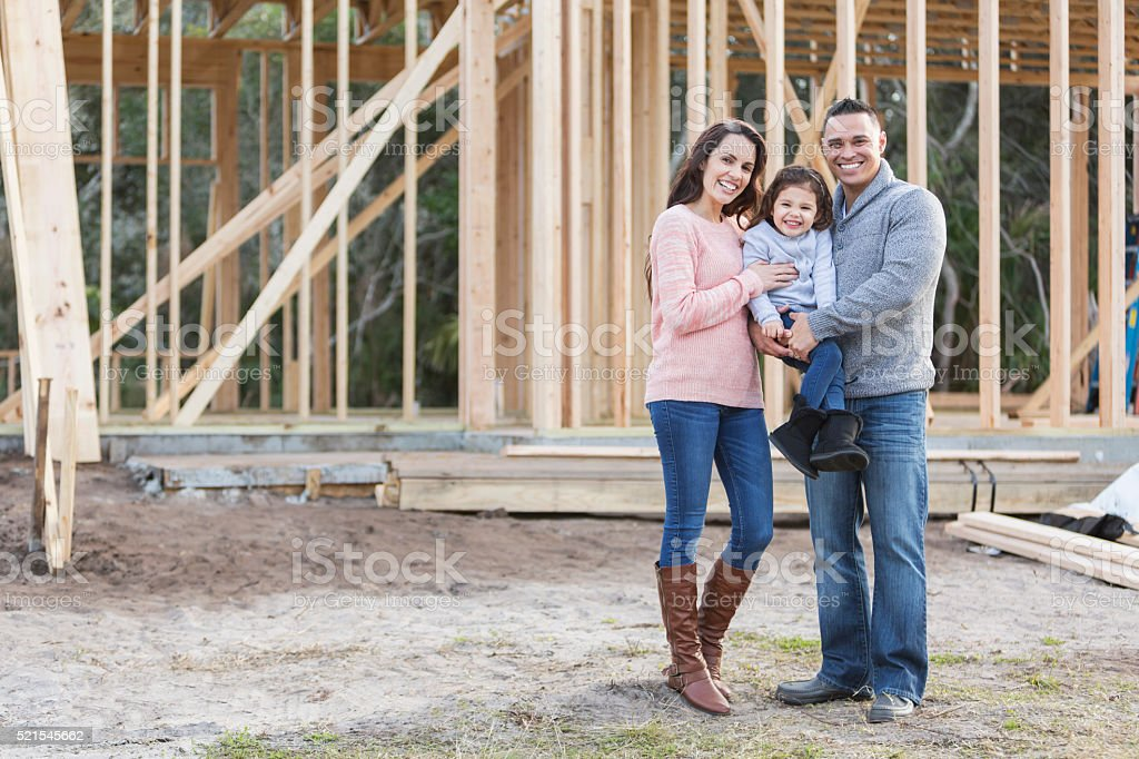 Hispanic family building a new home stock photo