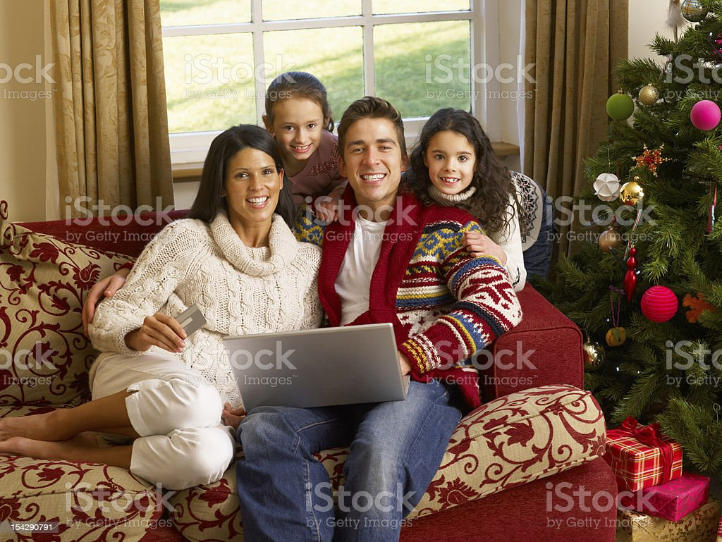 Hispanic family Christmas shopping online sitting on sofa in front of...