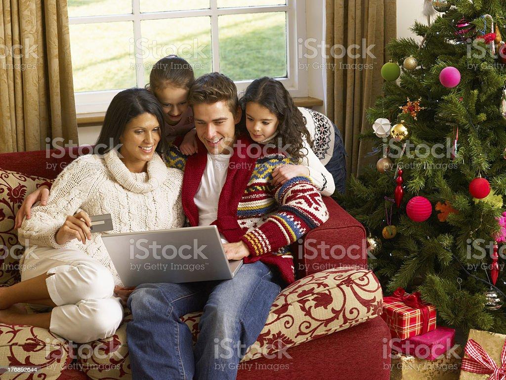 Hispanic family sitting in living room Christmas shopping online