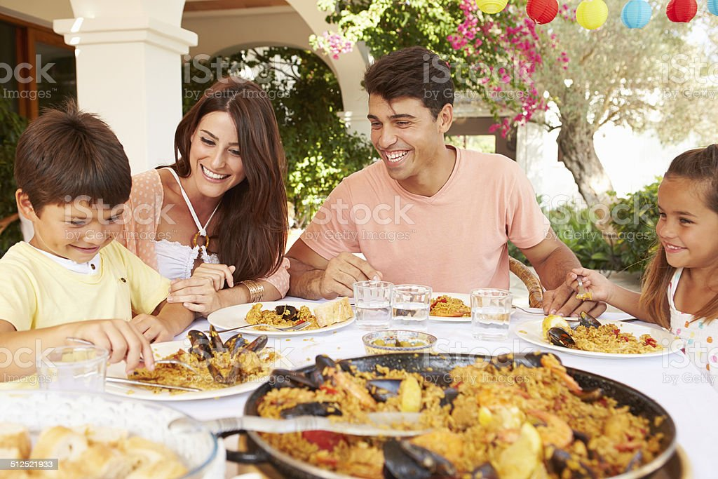 Hispanic Family Enjoying Outdoor Meal At Home Together stock photo