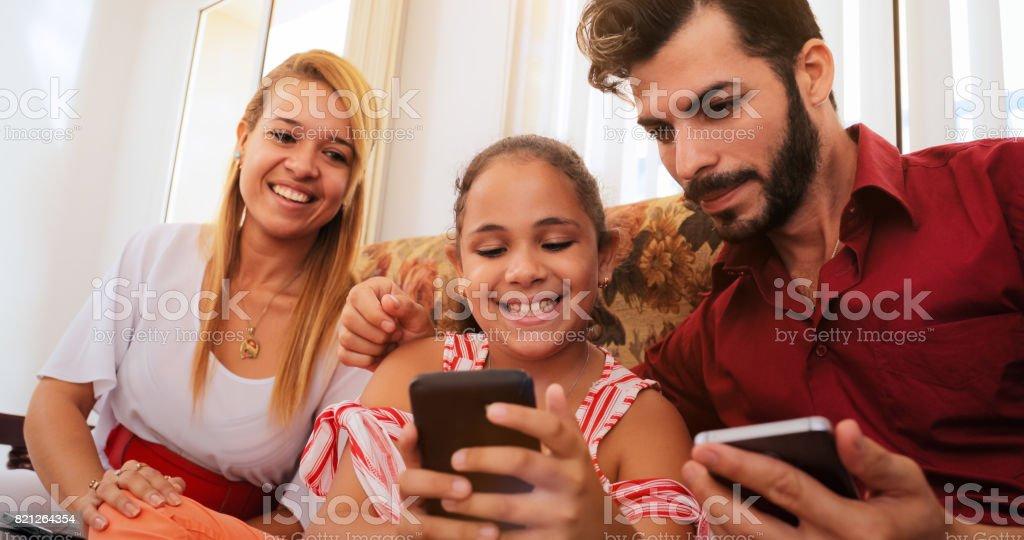 Hispanic Family Laughing Playing Game On Smartphone Telephone stock photo
