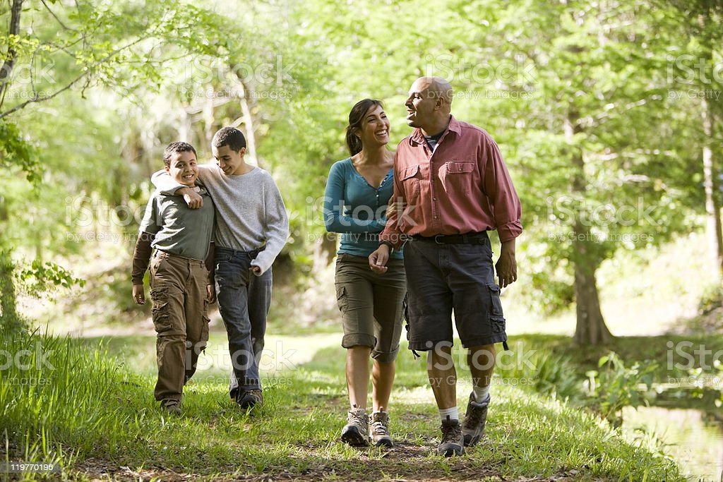 Hispanic family of four walking along trail in the park stock photo
