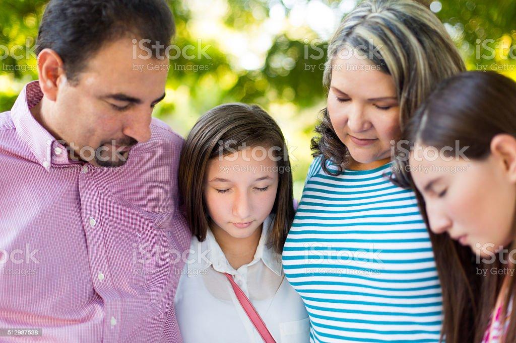 Hispanic family praying stock photo