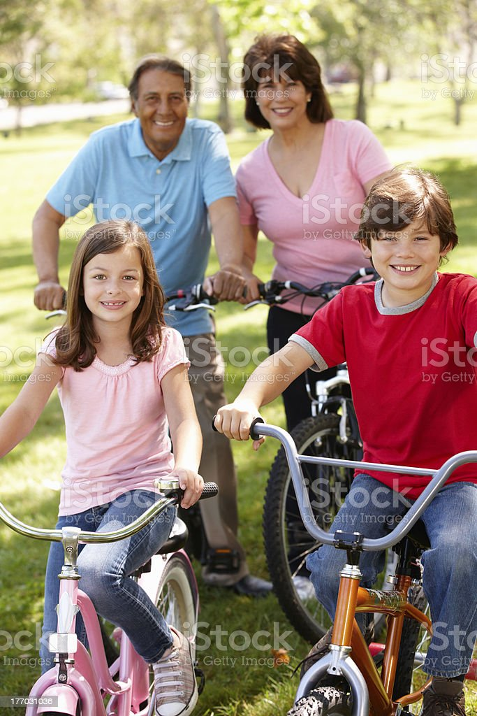 Hispanic family riding bikes in park royalty-free stock photo