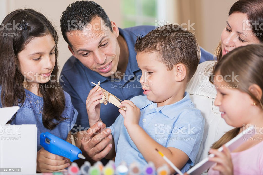 Hispanic family, three children doing project together stock photo