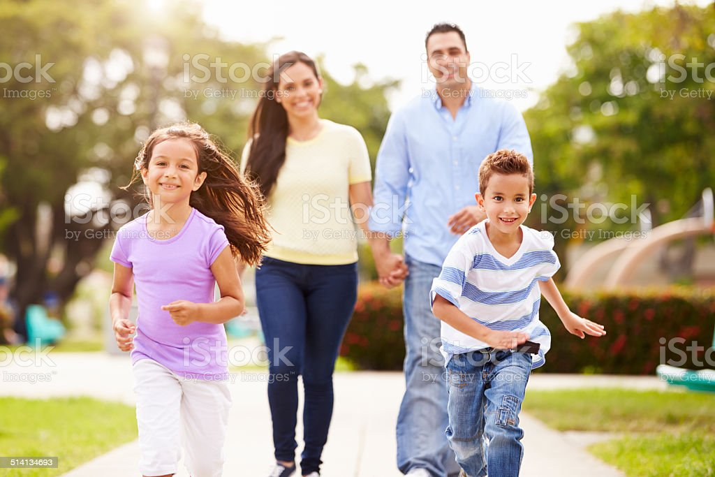 Hispanic Family Walking In Park Together stock photo