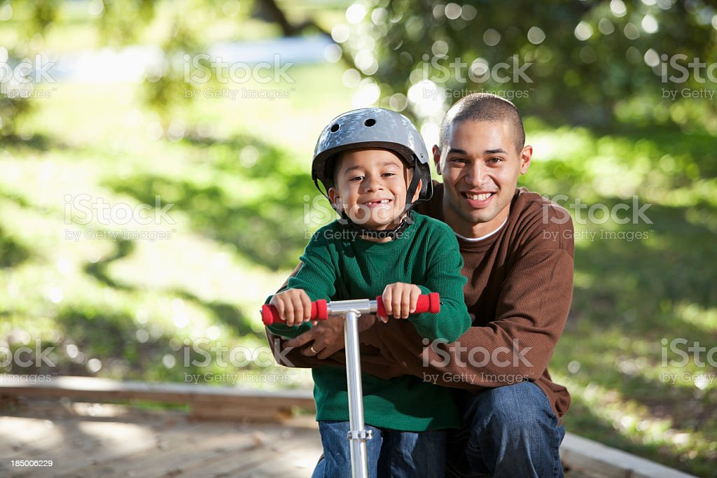 Hispanic father and boy on scooter in park stock photo