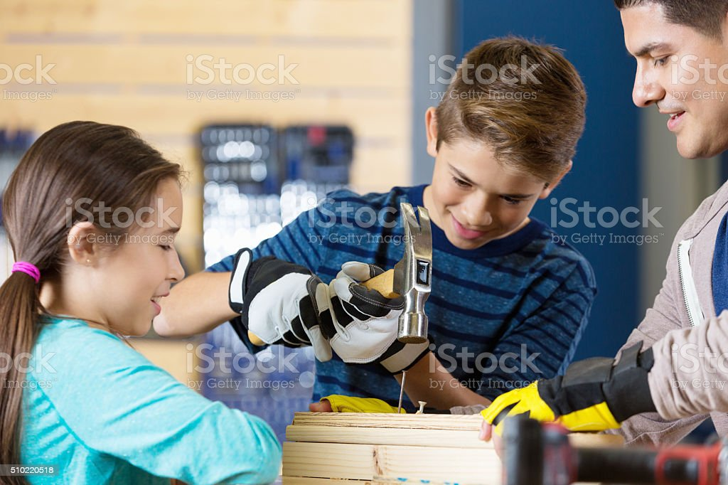 Hispanic father and children work on woodworking project stock photo