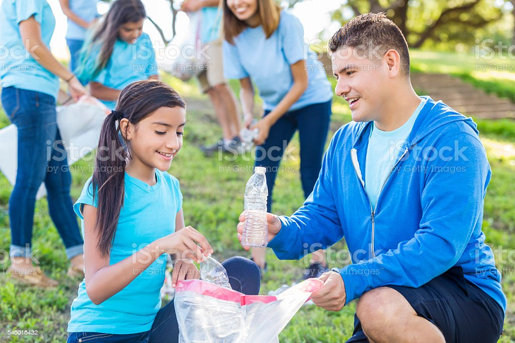 Hispanic father and daughter pick up trash in the park stock photo