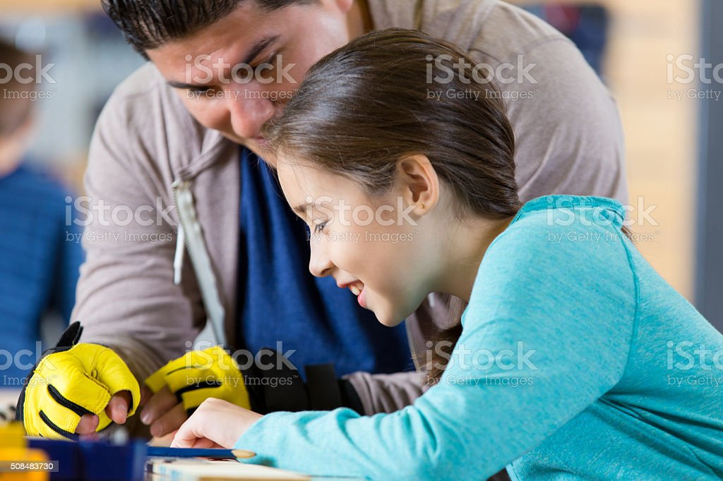 Hispanic father and daughter work together in workshop stock photo