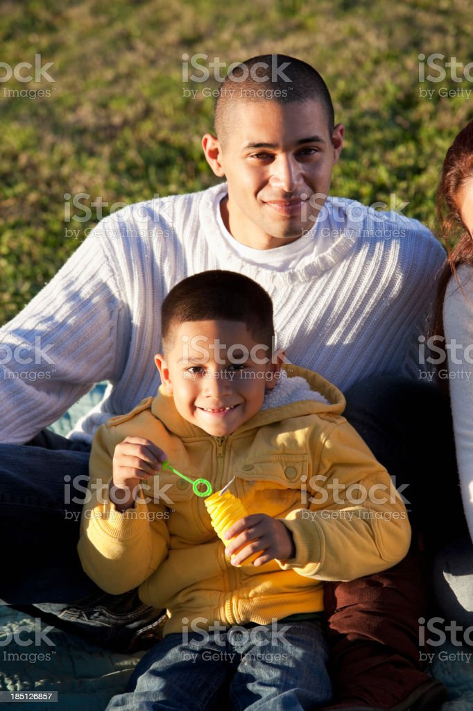 Hispanic father and son at park stock photo