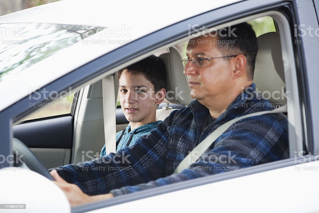 Hispanic father and son driving in car stock photo