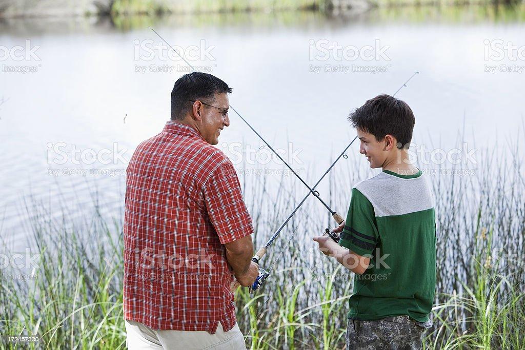 Hispanic father and son fishing royalty-free stock photo