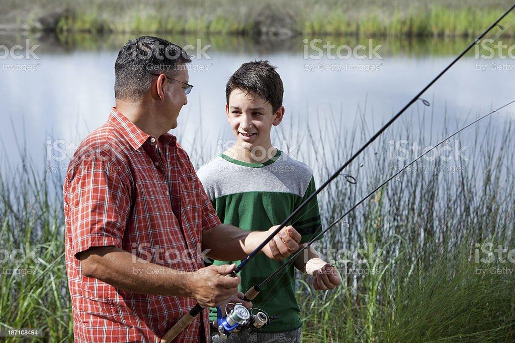 Hispanic father and son fishing stock photo