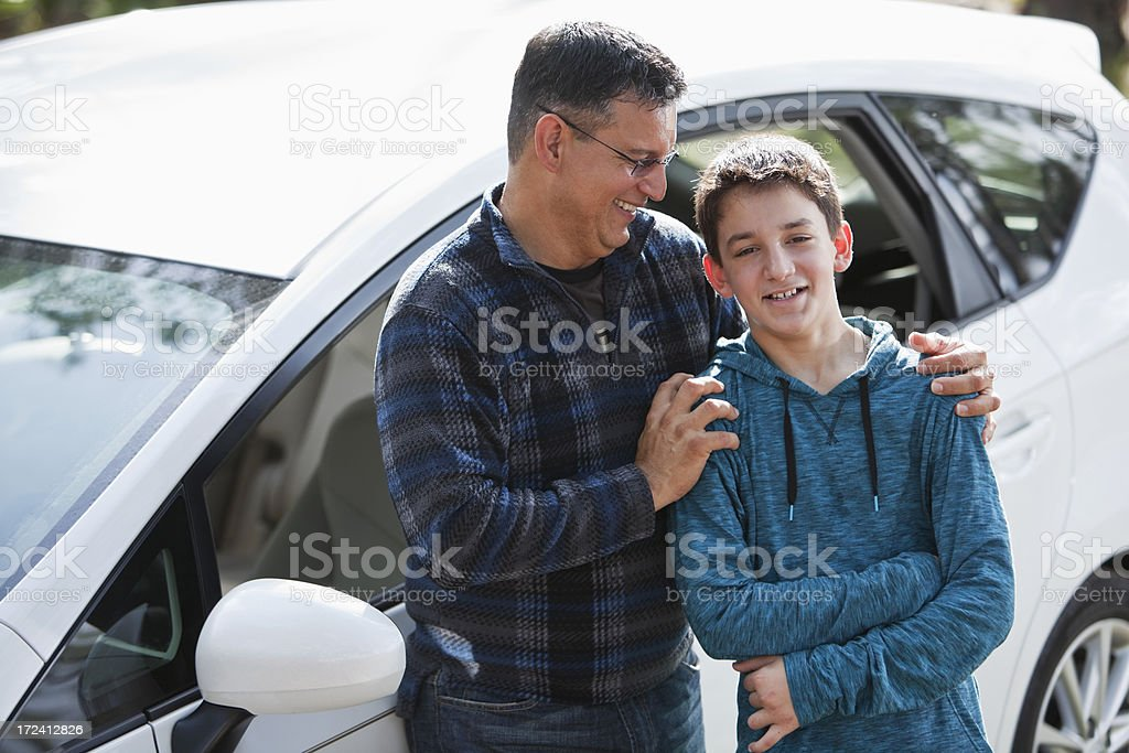 Hispanic father and son standing outside car stock photo