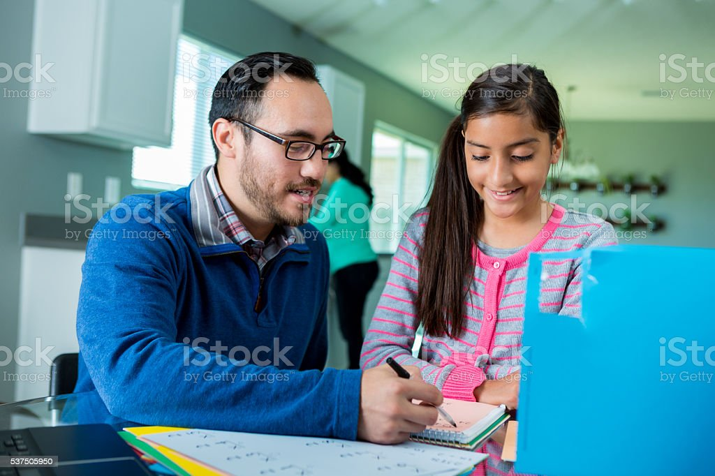 Hispanic father helps daughter with homework stock photo