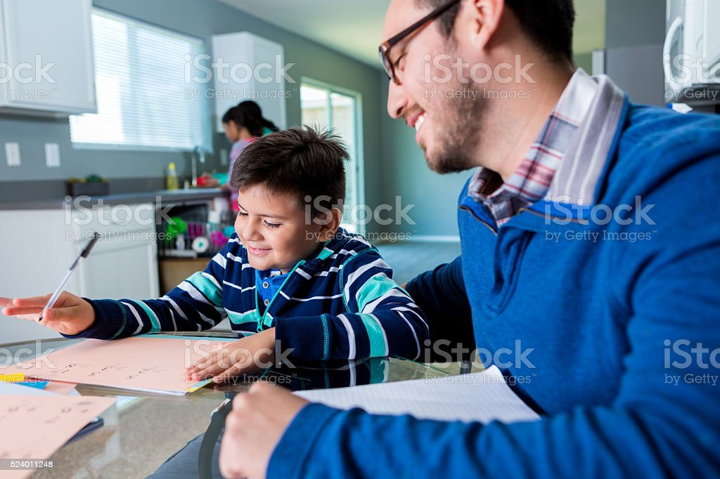 Hispanic father homeschools his elementary age son stock photo