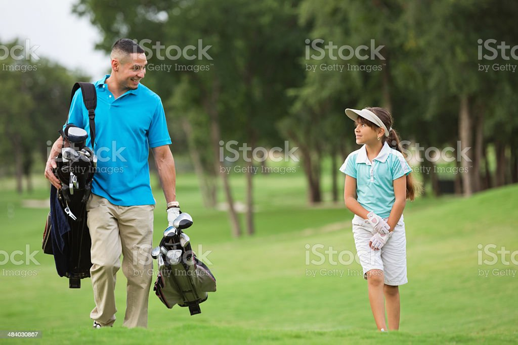 Hispanic father playing golf with preteen daughter on green course royalty-free stock photo