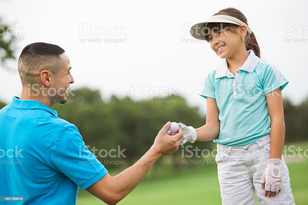 Hispanic father playing golf with young daughter stock photo