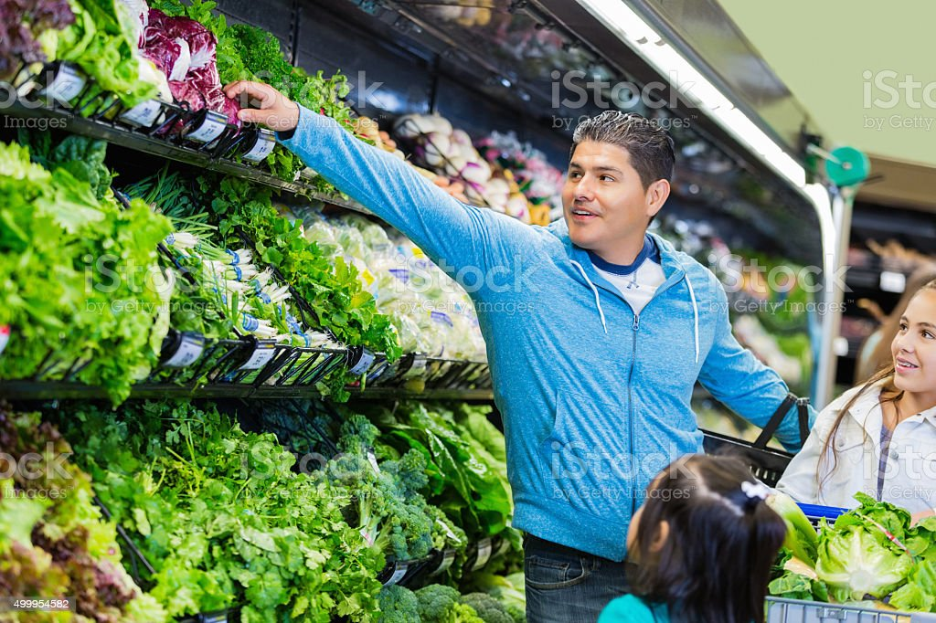 Hispanic father shopping for healthy food with young daughters stock photo