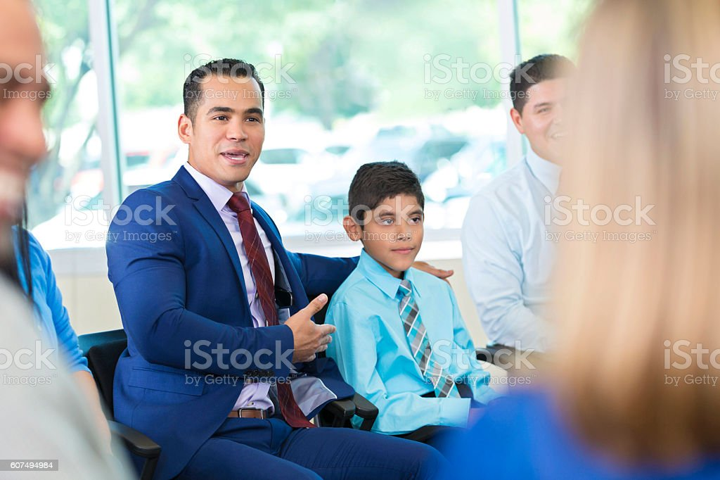 Handsome mid adult Hispanic man participates in a group therapy...