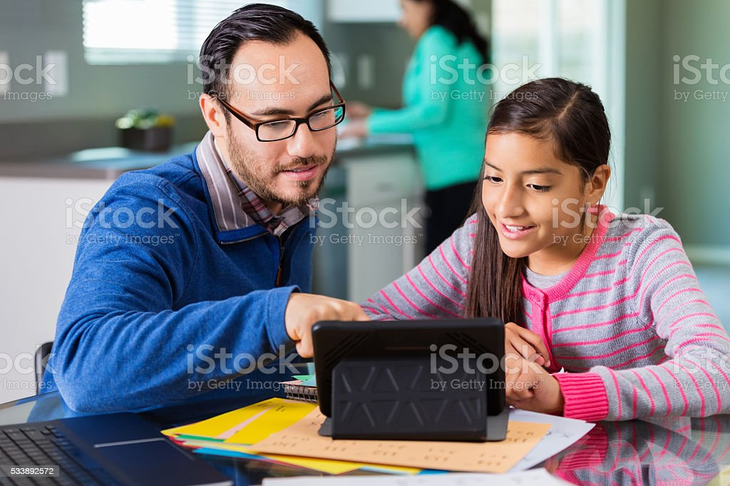 Hispanic father uses tablet to help daughter with homework stock photo