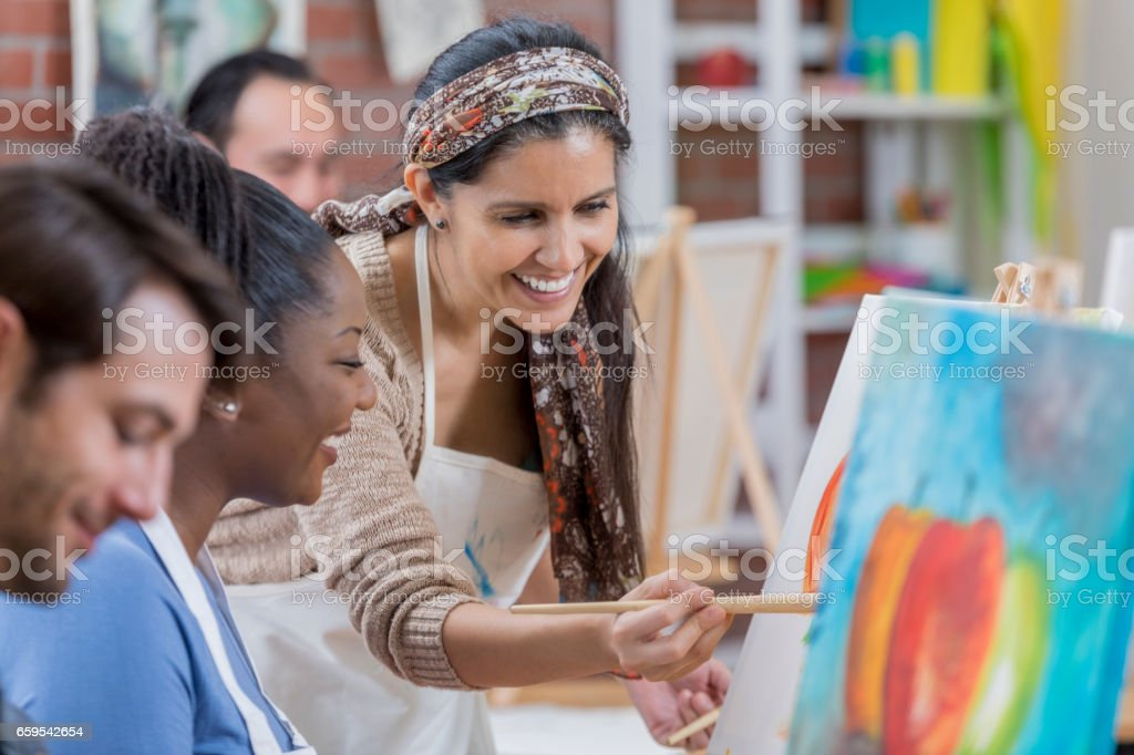 Hispanic female artist teaches painting class stock photo